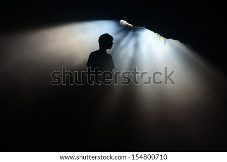 A silhouette of a person at a mine entrance with sunlight passing through.