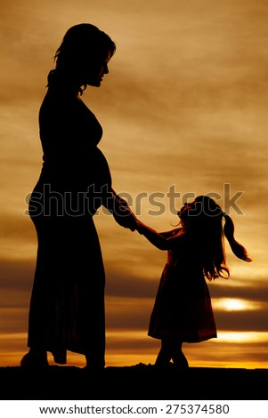 A silhouette of a pregnant mother holding on to her moms hands playing. - stock photo