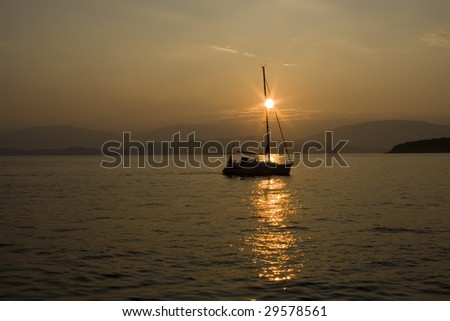 A silhouette of a sailboat in the sunrise