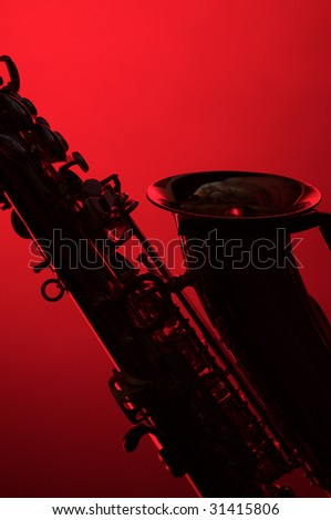 A silhouette of a saxophone close up isolated on a red background in the vertical format with copy space.