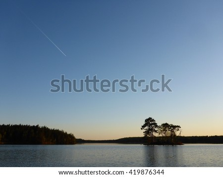 A silhouette of a small island and a forest at dusk with a white airplane line in the sky - stock photo