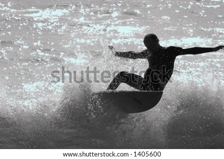 A silhouette of a surfer shredding the waves on the California coast.