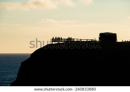 A silhouette of a tour bus parked on top of a cliff, overlooking the ocean. Image taken on Phillip Island, Australia on a summer evening. - stock photo