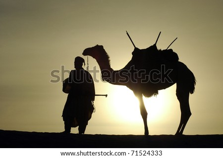 A silhouette of a Tuareg nomad standing next to his camel in the desert - stock photo