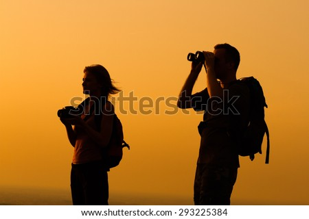 A silhouette of a woman and man with backpack looking at sunset.Couple with backpack watching the sunset - stock photo