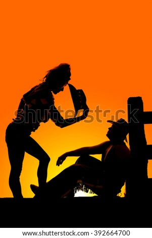 a silhouette of a woman bending down with her western hat off, looking at her cowboy who is sitting by the fence. - stock photo