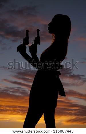 A silhouette of a woman blowing off the tip of her gun.