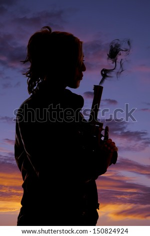 A silhouette of a woman blowing the smoke off  her pistol. - stock photo