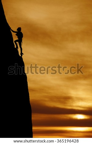 a silhouette of a woman climbing a mountain side with a backpack on. - stock photo