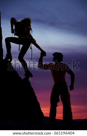 A silhouette of a woman climbing up a hill reaching back for the cowboy.