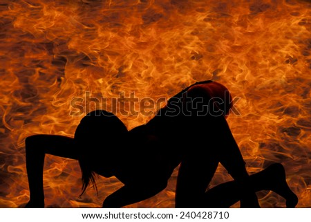 a silhouette of a woman crawling on the ground with flames behind her.