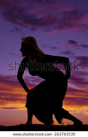 A silhouette of a woman crouching down in her sarong as she walks. - stock photo