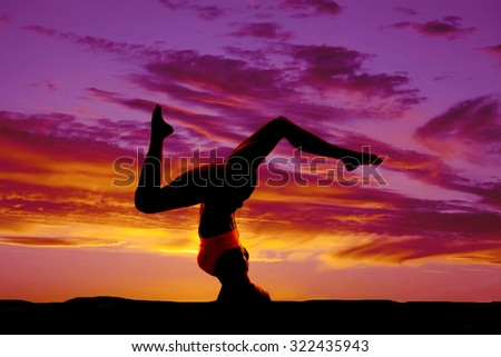 a silhouette of a woman doing a headstand in the outdoors.