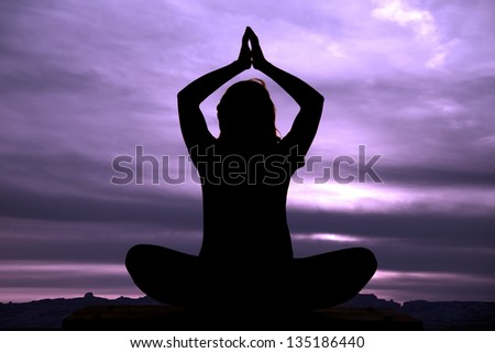 A silhouette of a woman doing a yoga pose in the outdoors