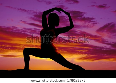 A silhouette of a woman doing a yoga stretch in the outdoors.