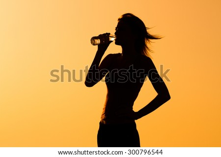 A silhouette of a woman drinking water.Refreshment - stock photo