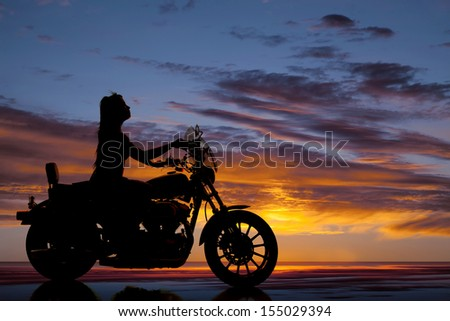 A silhouette of a woman driving down the road on her bike. - stock photo