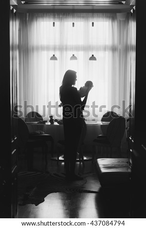 A silhouette of a woman holding a newborn in her arms - stock photo
