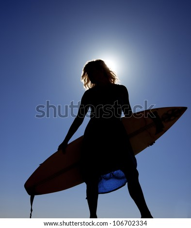 A silhouette of a woman holding her surf board with the blue sky and sun shining on her. - stock photo