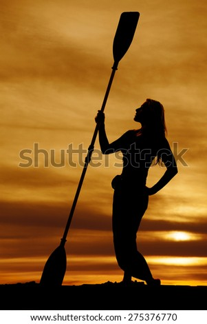 A silhouette of a woman holding on to her canoe paddle in the outdoors. - stock photo