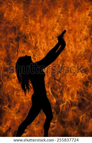 A silhouette of a woman holding on to her pistol with a fire flame background. - stock photo