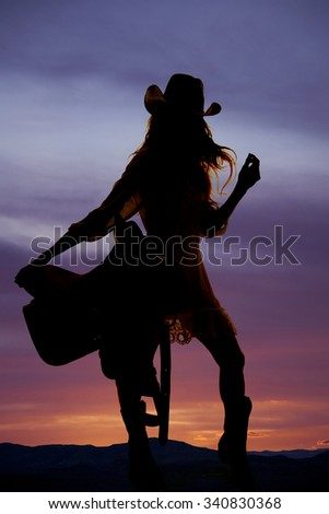 A silhouette of a woman holding on to her saddle with her hair blowing in the wind - stock photo