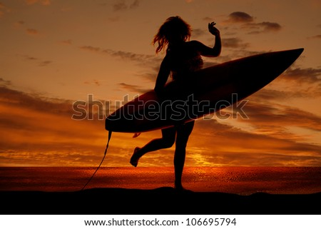 A silhouette of a woman holding on to her surf board running on the beach. - stock photo
