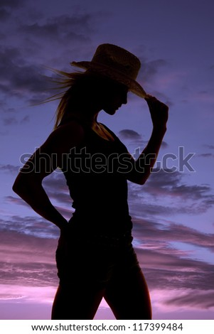 A silhouette of a woman holding on to the brim of her hat. - stock photo