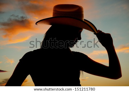 A silhouette of a woman holding on to the brim of the hat