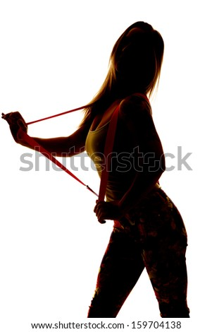 a silhouette of a woman holding out her suspenders. - stock photo
