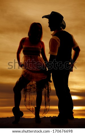 a silhouette of a woman holding up her dress looking at her cowboy. - stock photo