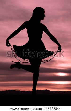 A silhouette of a woman holding up her dress with her foot up - stock photo