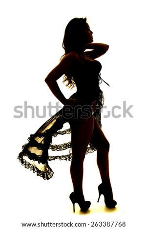 A silhouette of a woman in her black sheer lingerie standing. - stock photo