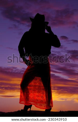 a silhouette of a woman in her dress and cowgirl hat. - stock photo