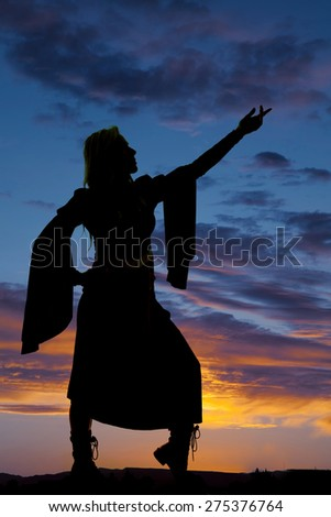 A silhouette of a woman in her dress with her arms up. - stock photo