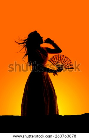 a silhouette of a woman in her fancy dress, with the wind blowing holding on to her fan. - stock photo
