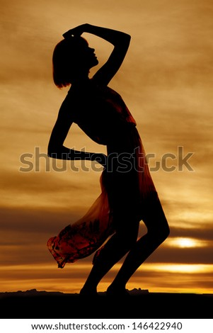 A silhouette of a woman in her flowing dress leaning back - stock photo