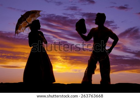 A silhouette of a woman in her formal dress with her umbrella standing next to her cowboy. - stock photo