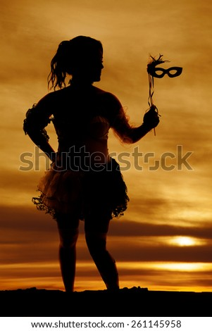 a silhouette of a woman in her Halloween costume with a mask. - stock photo
