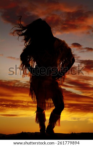 a silhouette of a woman in her Indian clothing with the wind blowing her hair. - stock photo