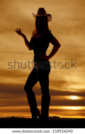 A silhouette of a woman in her jeans, boots, and hat standing in the outdoors with her hand up. - stock photo