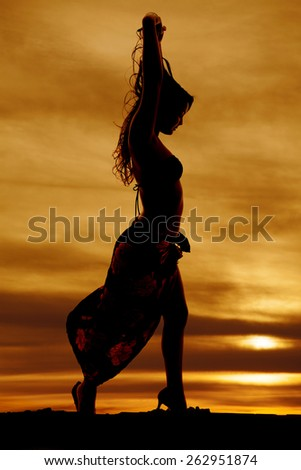 A silhouette of a woman in her sarong and bikini with her hands in her hair. - stock photo