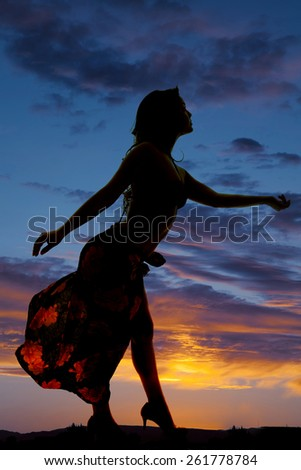 A silhouette of a woman in her sarong reaching out and dancing. - stock photo