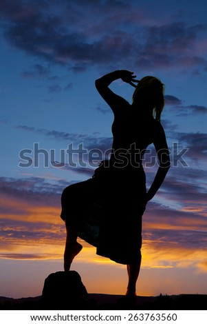 A silhouette of a woman in her sarong with her toe on a rock. - stock photo