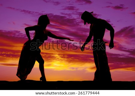 A silhouette of a woman in her sexy clothing reaching out to her cowboy. - stock photo