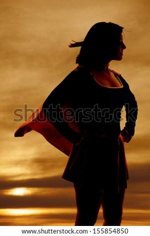 A silhouette of a woman in her super hero out fit cape flying. - stock photo
