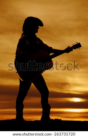 A silhouette of a woman in her western clothing playing her guitar. - stock photo