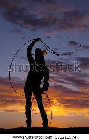 A silhouette of a woman in her western hat with her rope in the air