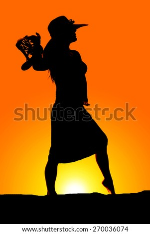 A silhouette of a woman in the outdoors holding on to her sandals. - stock photo