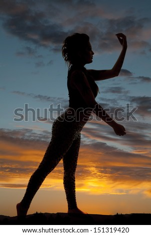 A silhouette of a woman in the sunset. - stock photo